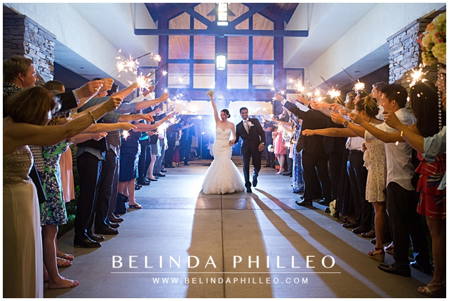 bride and groom exit down a row of guests with sparklers