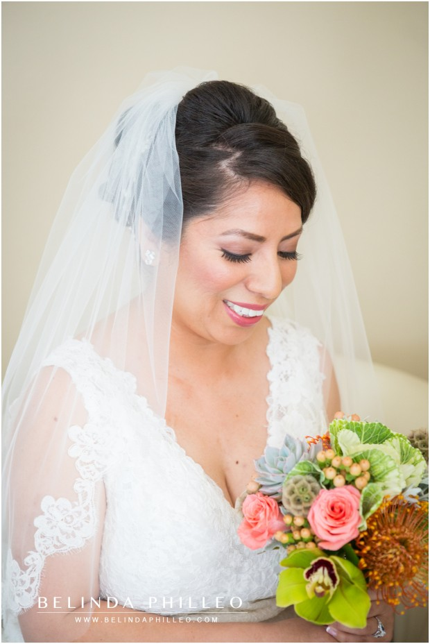 a bride admires her bouquet of pink and green succulents and roses
