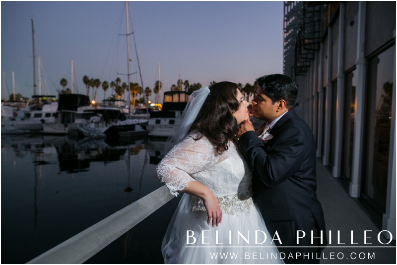 Bride and groom share a kiss during a romantic sunset at The Portofino Hotel and Marina, Redondo Beach, CA