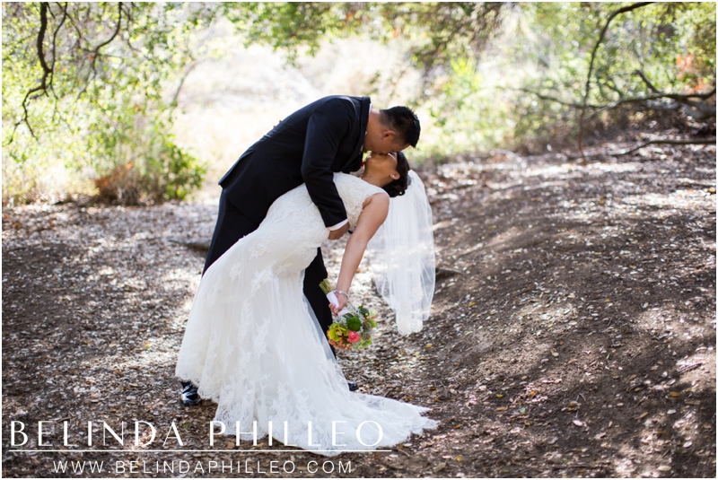 Groom dips and kisses his bride in Malibu, CA