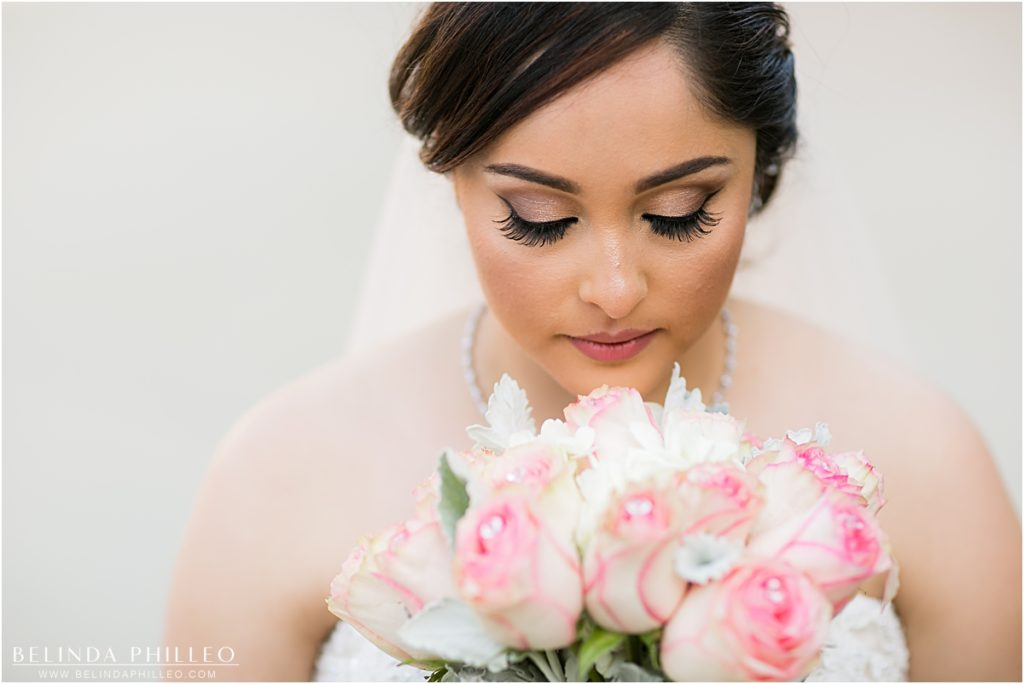 bride admires her pink and white bouquet