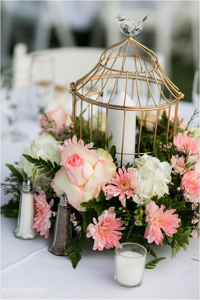 pink and white flowers surround a birdcage centerpiece at Kellogg House wedding reception, Cal Poly, CA