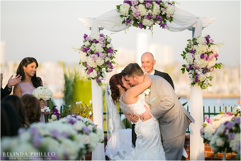 Bride and groom share their first kiss at The Reef Restaurant, Long Beach, CA. Photography by Belinda Philleo.
