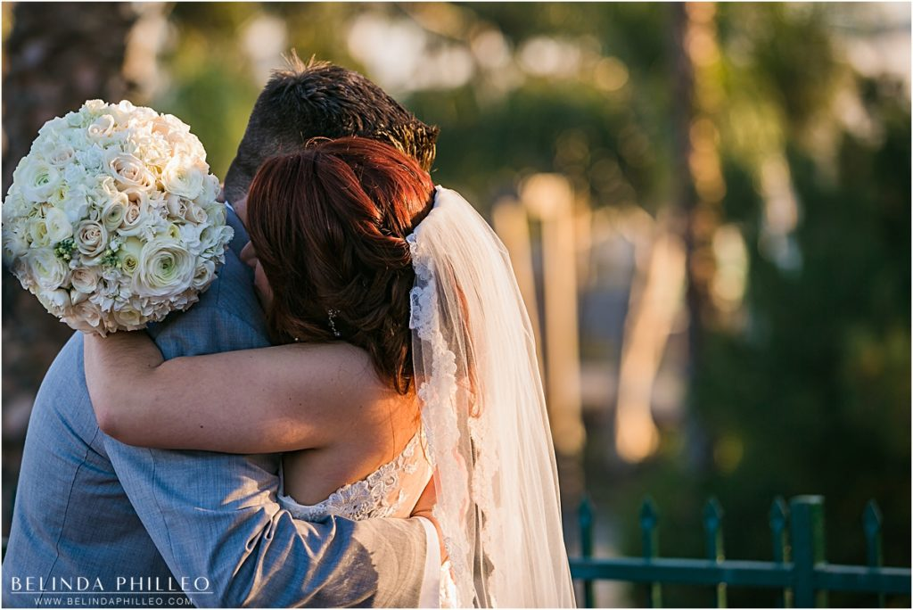 Bride and groom share an emotional hug moments after saying I do at the Reef Restaurant, Long Beach, CA