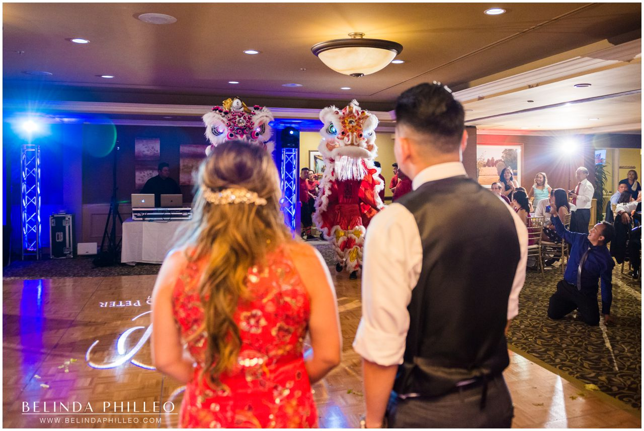 Bride and Groom entertained by Lion Dance at their Friendly Hills Country Club Wedding in Whittier, CA. Photo by Belinda Philleo
